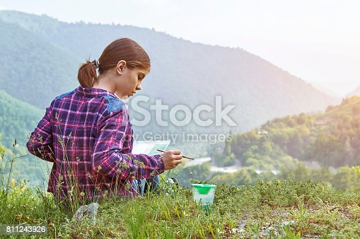 istock Cute teenager girl drawing with paintbrush in beautiful mountain place 811243926