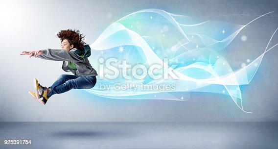 istock Cute teenager jumping with abstract blue scarf around her 925391754