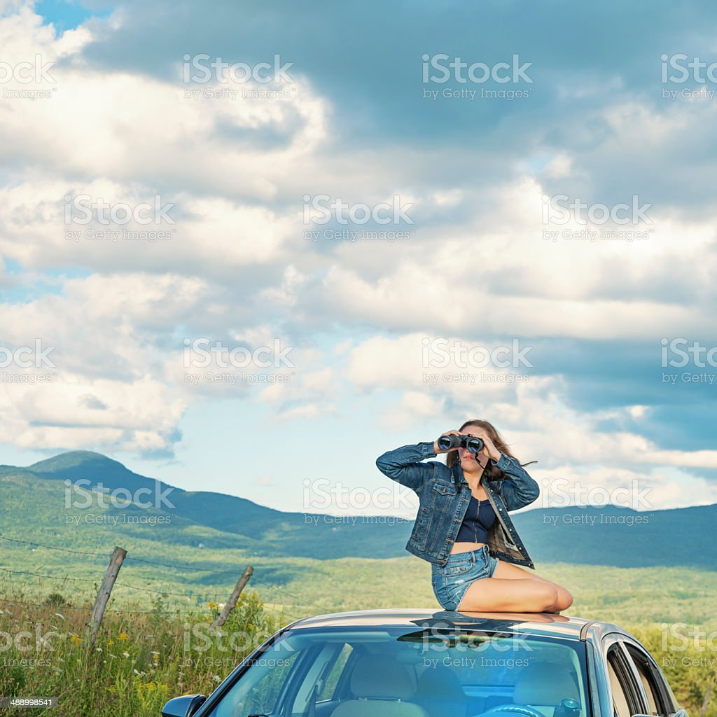 Cute teenager with binocular on top of car, rural road. stock photo