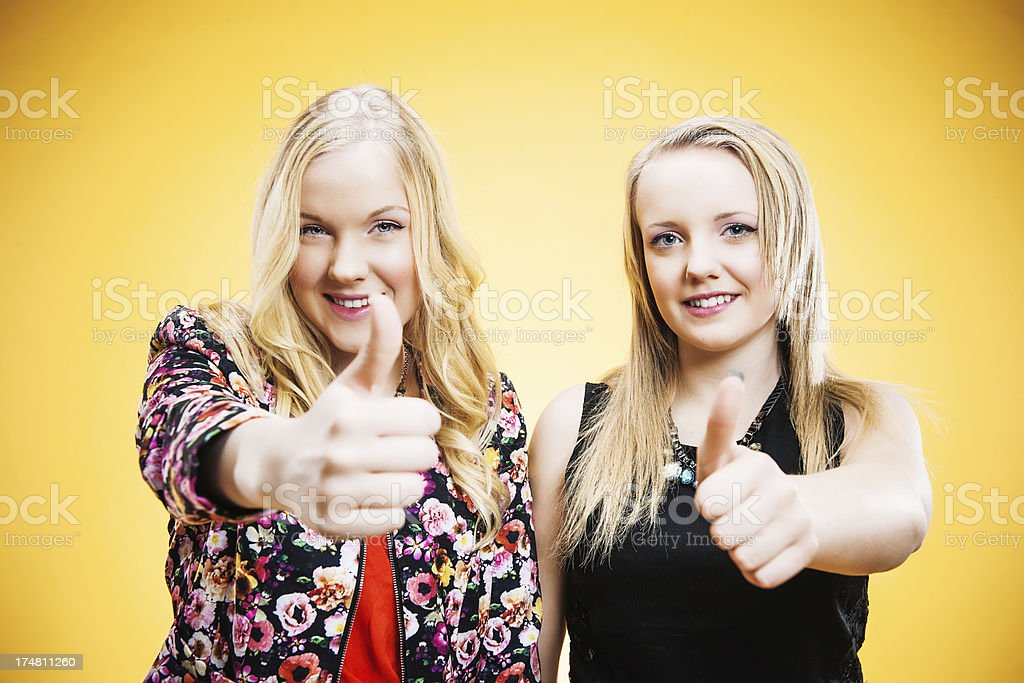 Cute teenagers doing thumbs up royalty-free stock photo