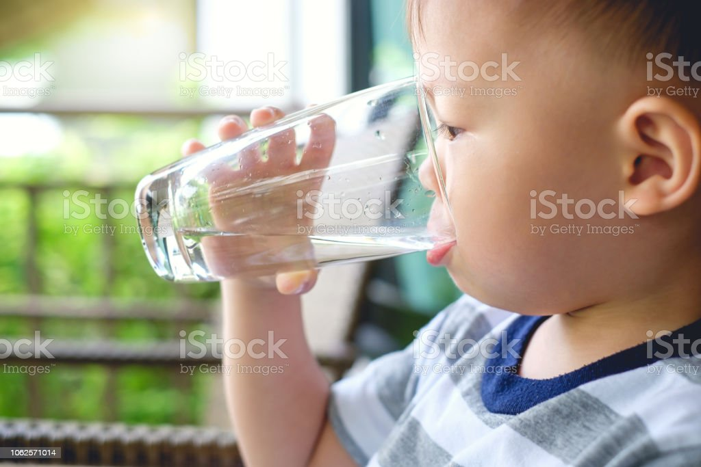 Cute thirsty little Asian 2 years old toddler baby boy child holding and drinking glass of water by himself royalty-free stock photo