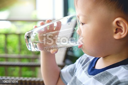 Cute thirsty little Asian 2 years old toddler baby boy child holding and drinking glass of water by himself against green background near home garden, best beverages for child's health concept