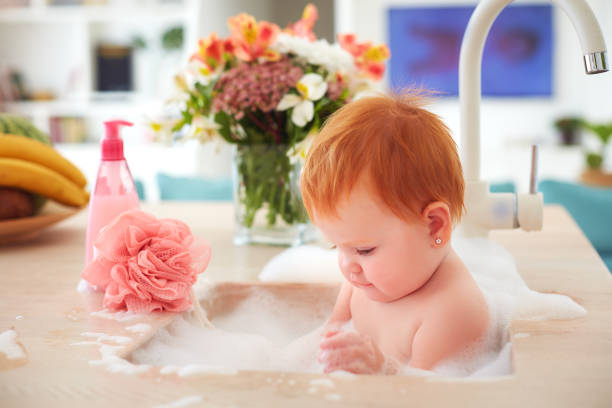 cute tiny baby girl taking a bubble bath in a kitchen sink stock photo