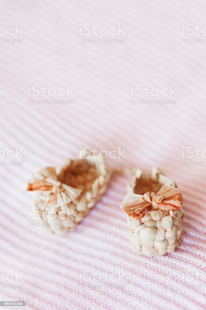 Cute tiny sandals made of straw, ancient traditional russian type of footwear. Natural booties for baby girl with a bow on pink knitted fabric background. - Royalty-free Baby Booties Stock Photo
