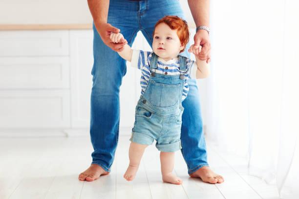 niedlichen kleinkind baby boy mit hilfe des vaters laufen lernen - jeans overall stock-fotos und bilder