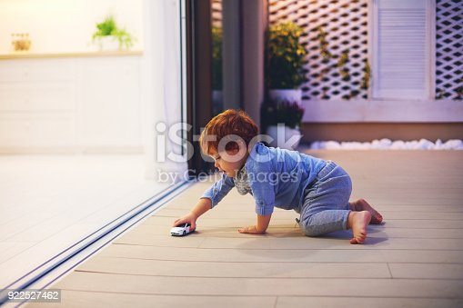 istock cute toddler baby boy playing with toy car at the patio with open space kitchen and sliding doors 922527462