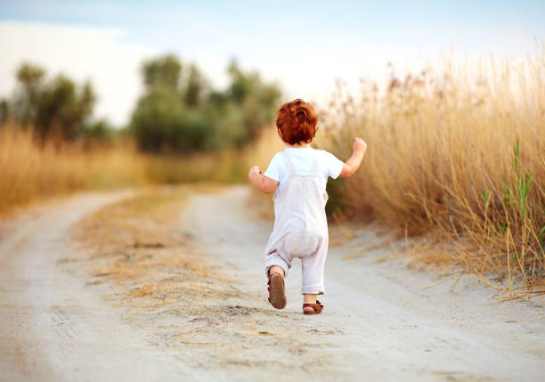 cute toddler baby boy running away along the path at summer field cute toddler baby boy running away along the path at summer field bib overalls boy stock pictures, royalty-free photos & images