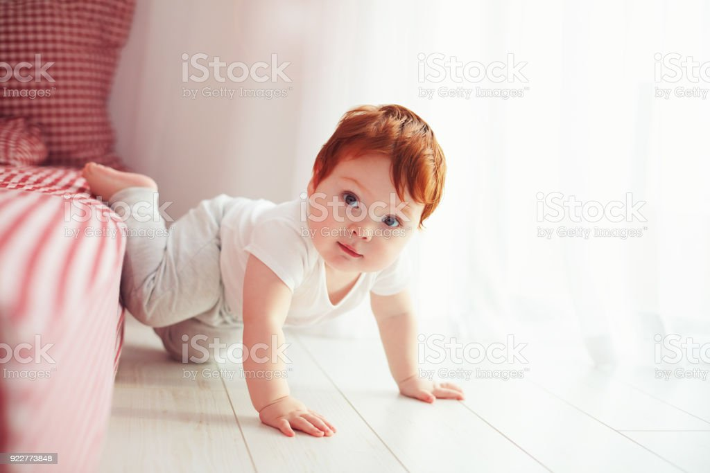 cute toddler baby getting off the bed, crawling at home stock photo
