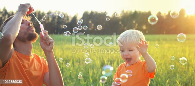 Cute toddler blond boy and his father playing with soap bubbles on summer field. Beautiful sunset light. Happy childhood concept. Authentic lifestyle image.