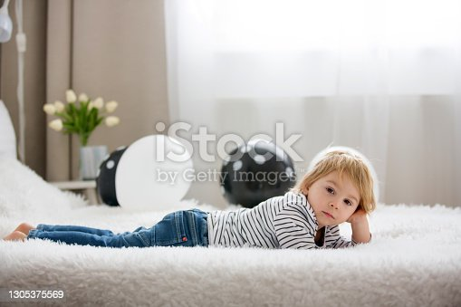 istock Cute toddler blond child, baby boy, lying in bed with balloons, smiling at camera 1305375569