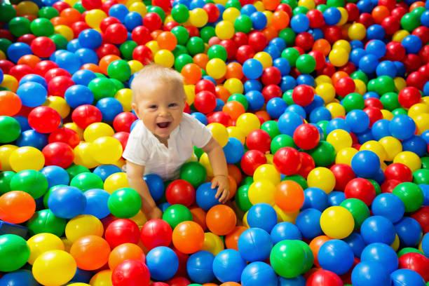 Niño lindo muchacho, niño, jugando en bolas coloridas en parque infantil - foto de stock