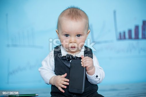 istock Cute toddler boy, dressed in suit and bow, talking on the phone and playing on tablet 954196298