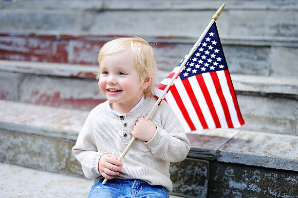 Cute toddler boy holding american flag stock photo