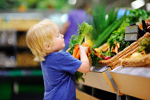 Cute toddler boy in supermarket choosing fresh organic carrots stock photo