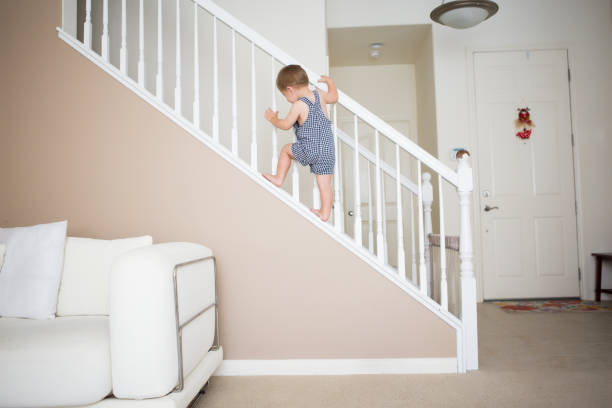 cute toddler boy is climbing the stairways at home. - danger stock pictures, royalty-free photos & images