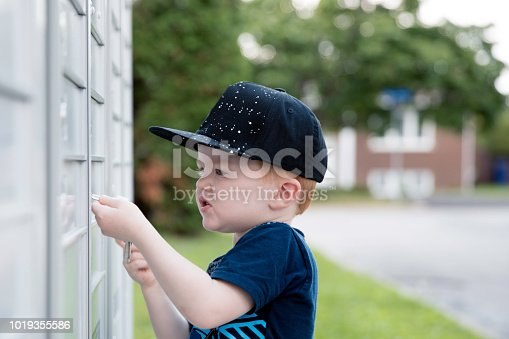 istock Cute Toddler Boy Picking up the Mail at Postal Mailbox 1019355586