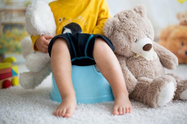 可愛的幼兒男孩,便盆訓練,玩他的泰迪熊 - 四肢 身體部份 個照片及圖片檔