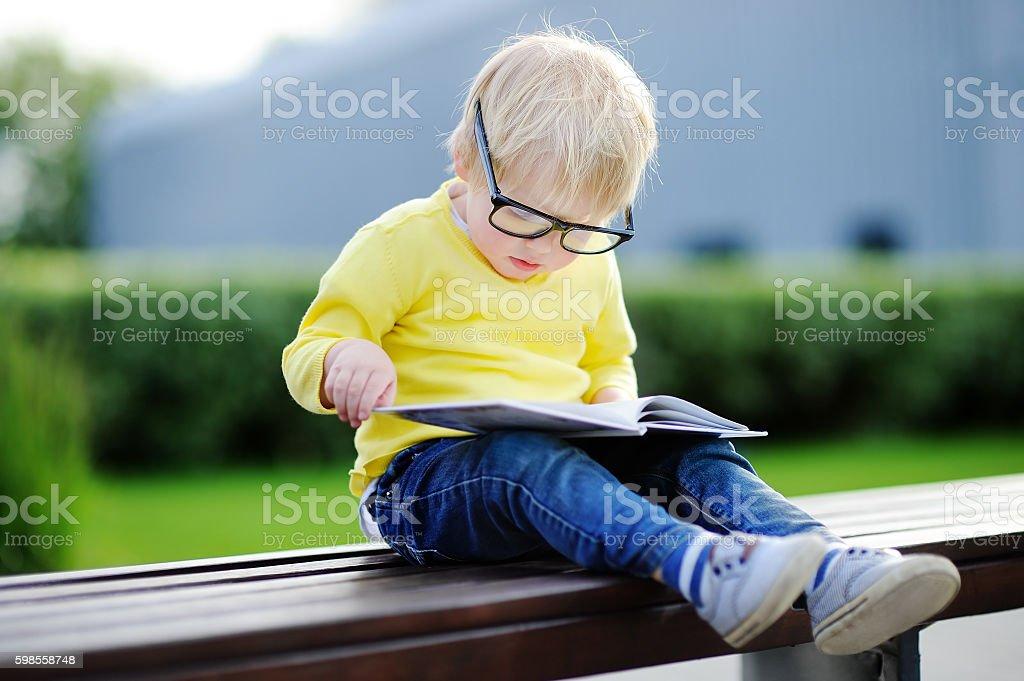 Cute toddler boy reading a book outdoors stock photo