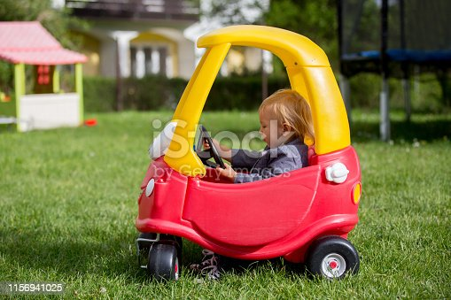 istock Cute toddler boy, riding big plastic red car toy in the park 1156941025
