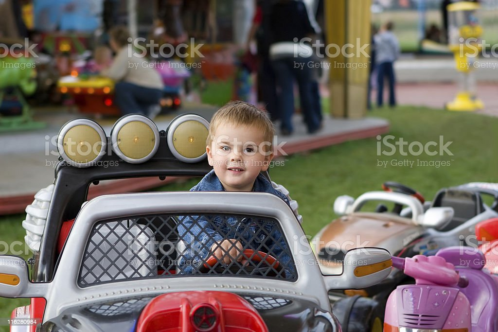 Cute toddler boy riding on a merry-go-round stock photo