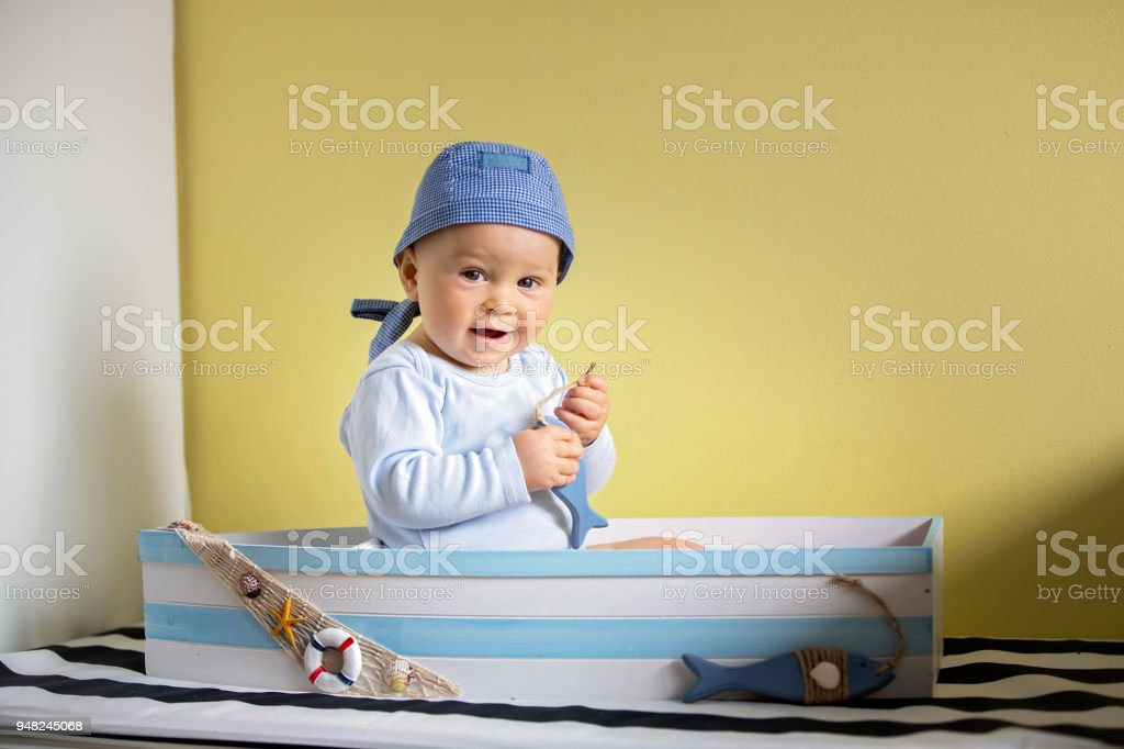Cute toddler boy, sitting in a big wooden boat at home, playing with wooden fishes stock photo