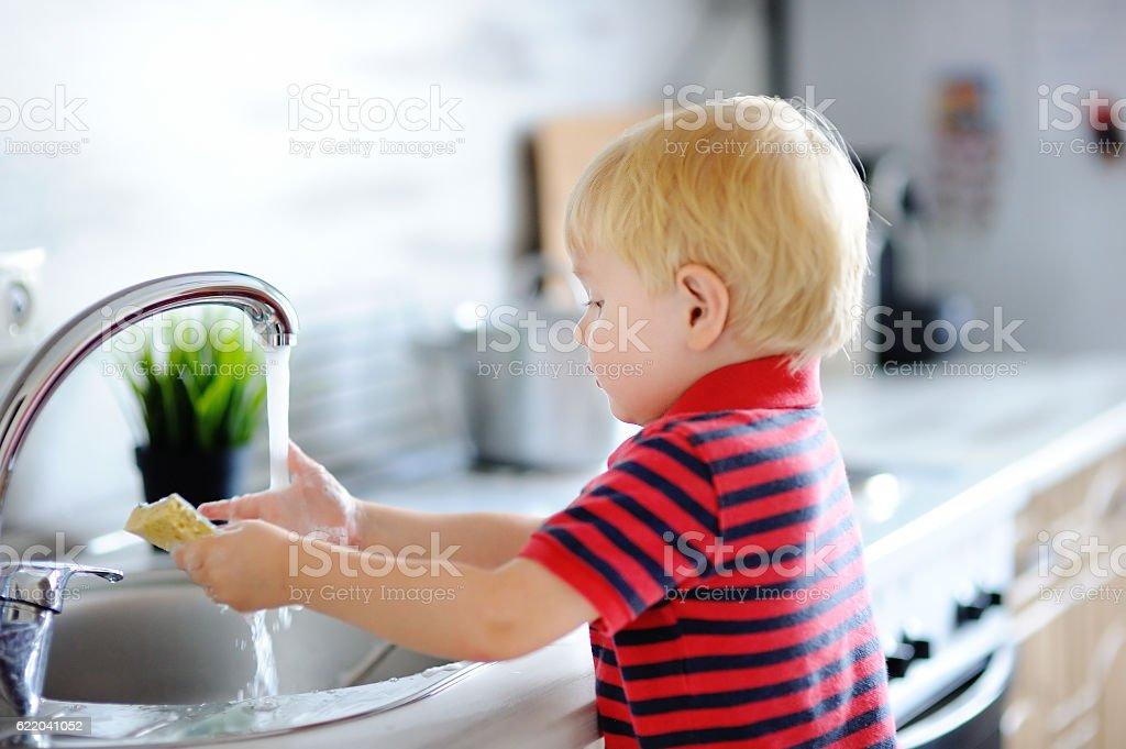 Cute toddler boy washing dishes in domestic kitchen - foto de stock