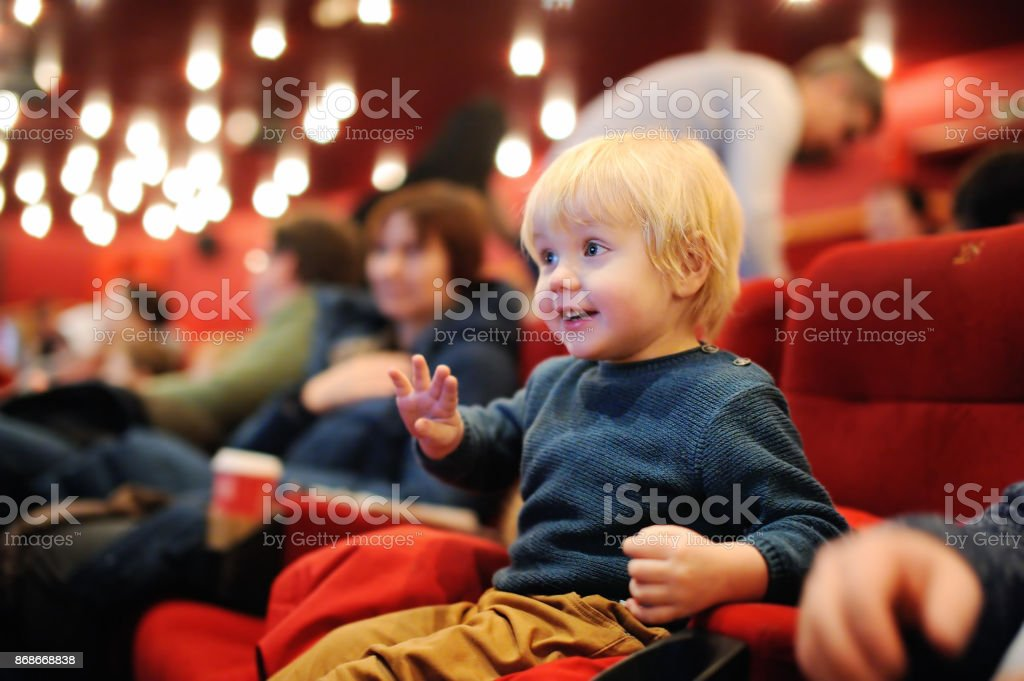 Cute toddler boy watching cartoon movie in the cinema stock photo