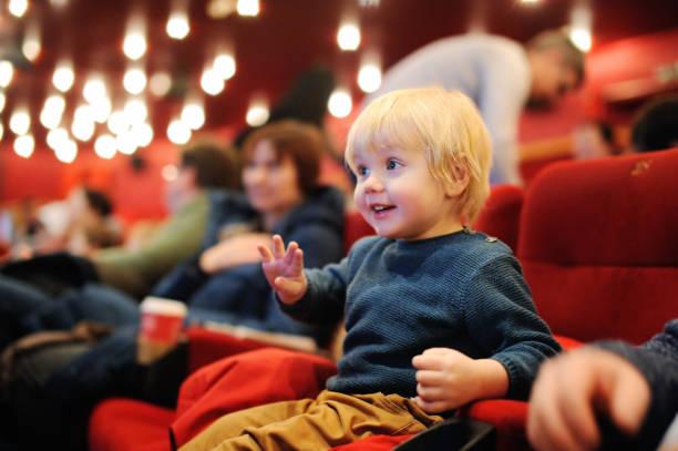 Cute toddler boy watching cartoon movie in the cinema stock photo