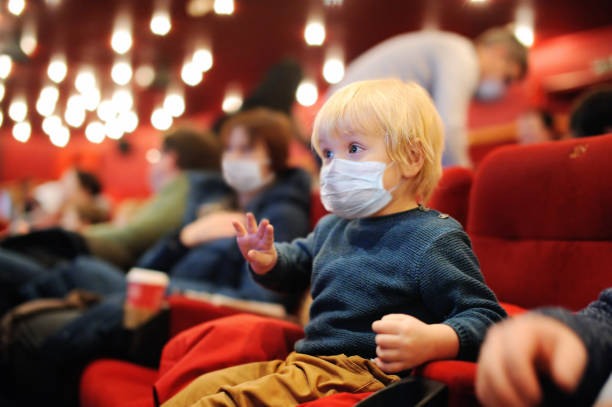 Cute toddler boy wearing face mask watching cartoon movie in the cinema after quarantine. Lifting virus lockdown. Social distancing restrictions remain. stock photo