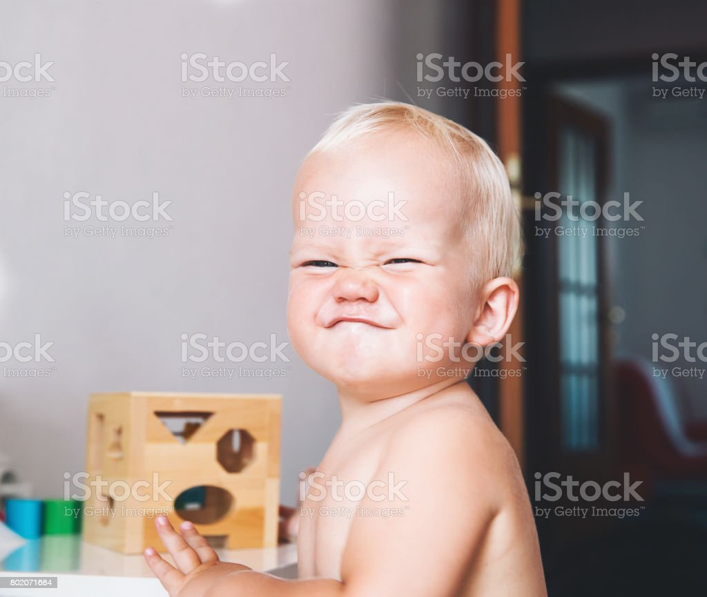Cute toddler frowns and expresses disagreement on his face. stock photo