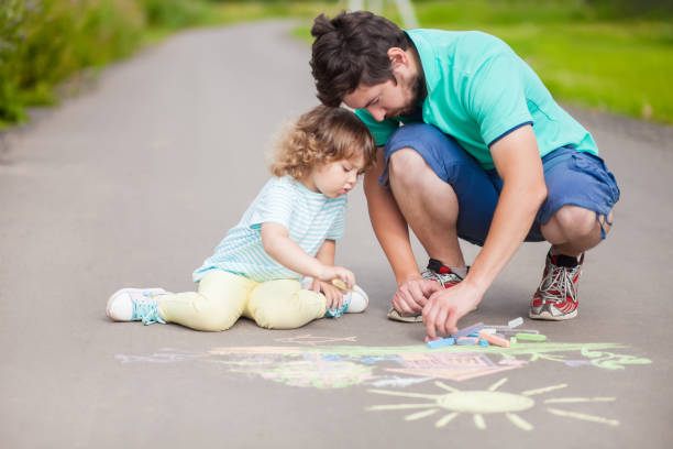 Cute toddler girl and her father drawing with color chalk. stock photo