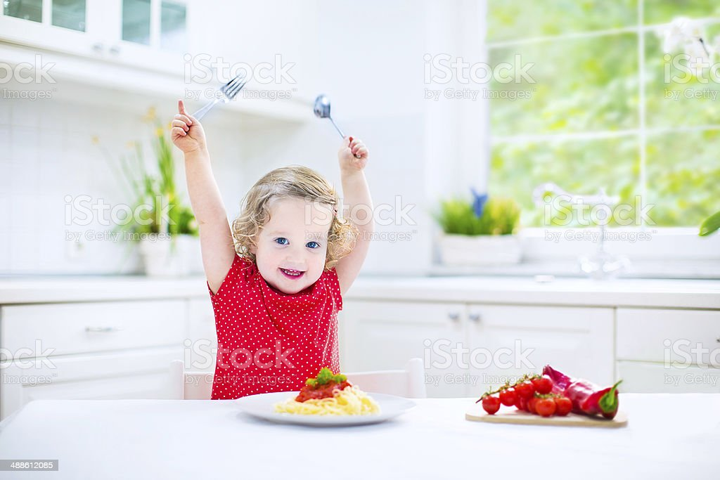 Cute toddler girl eating spaghetti in a white kitchen stock photo