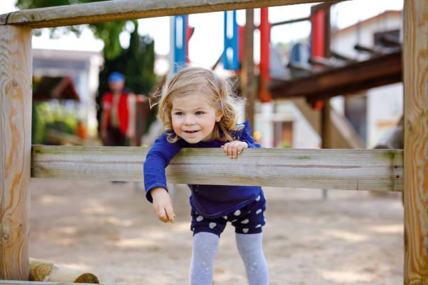 Niedliches Kleinjunglermädchen, das sich auf dem Spielplatz vergnüglichen. Fröhliches, gesundes kleines Kinderklettern, Schwingen und Rutschen auf verschiedenen Geräten. Am sonnigen Tag in bunten Kleidern. Aktive Spiele im Freien für Kinder – Foto