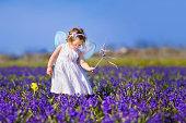 かわいい幼児の女の子の妖精のコスチュームのフラワーフィールド