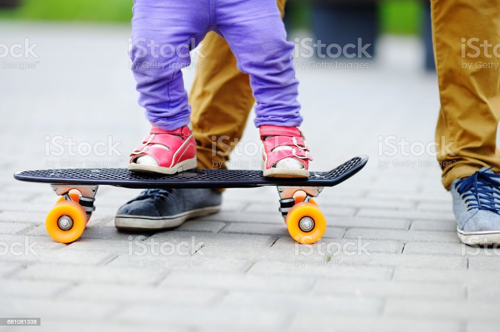 Cute toddler girl learning to skateboard with her father outdoors royalty-free stock photo