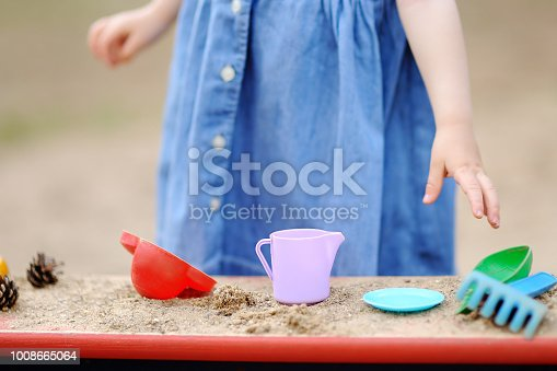 Cute toddler girl playing in a sandbox with moulds and pinecones. Outdoors game for little kids. Developing activities for child