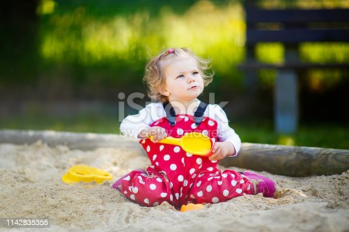 Cute toddler girl playing in sand on outdoor playground. Beautiful baby in red gum trousers having fun on sunny warm summer day. Child with colorful sand toys. Healthy active baby outdoors plays games.
