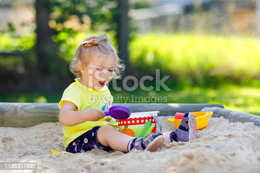 Cute toddler girl playing in sand on outdoor playground. Beautiful baby having fun on sunny warm summer sunny day. Happy healthy child with sand toys and in colorful fashion clothes