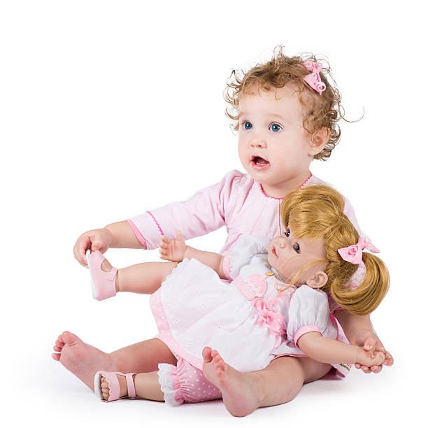 niedlichen kleinkind mädchen spielt mit ihr erstes doll - geburtstagsgeschenke für beste freundin stock-fotos und bilder