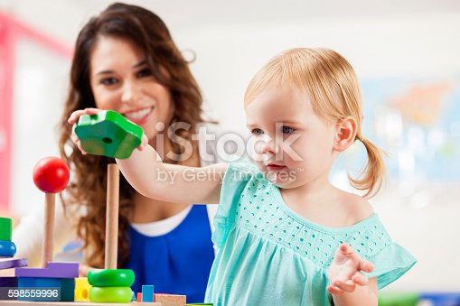 istock Cute toddler girl playing with learning blocks in daycare 598559996