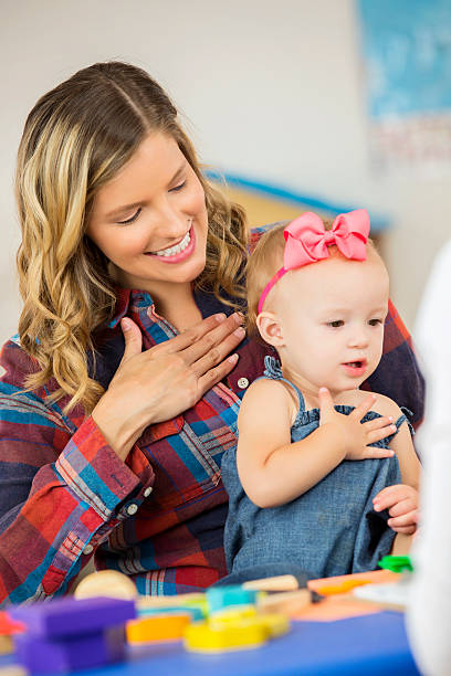 Cute toddler girl practicing sign language with her mother stock photo