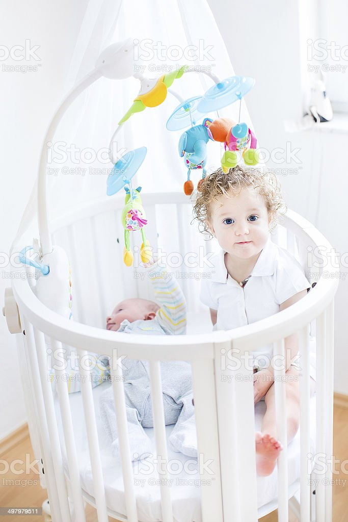 Cute toddler girl sitting in crib of her newborn brother royalty-free stock photo