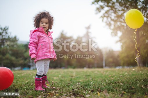 istock Cute toddler girl with Afro hair standing outside with balloons 626914246