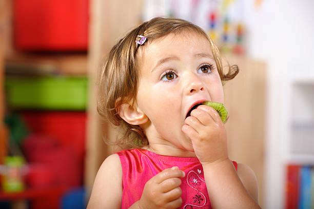 Niedliche Kleinkinder hat einen gesunden Snack im Kinderzimmer – Foto