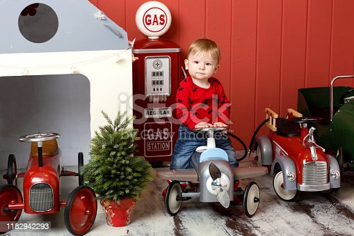 486524205 istock photo Cute toddler is playing with toy cars. Rides a toy typewriter airplane. Happy childhood 1182942293