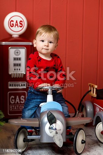 486524205 istock photo Cute toddler is playing with toy cars. Rides a toy typewriter airplane. Happy childhood 1182942296