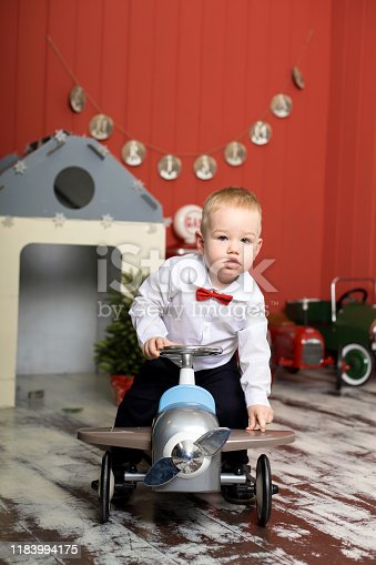 486524205 istock photo Cute toddler is playing with toy cars. Rides a toy typewriter airplane. Happy childhood 1183994175