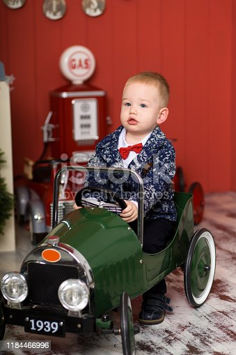 486524205 istock photo Cute toddler is playing with toy cars. Rides a toy typewriter airplane. Happy childhood 1184466996