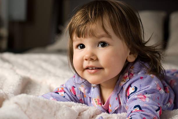 niedliche kleinkinder auf dem bett - lila mädchen zimmer stock-fotos und bilder
