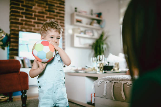 Cute Toddler Playing With Soccer Ball In Domestic Room Cute Toddler Playing With Soccer Ball In Domestic Room bib overalls boy stock pictures, royalty-free photos & images